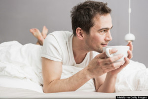 Mid adult man lying on front on bed, holding coffee cup